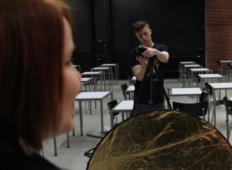 Lari Koponen säätää kameraa ja Roosa Jarkko odottelee kuvaussession alkamista. Larin edessä on reflektori, jokka kasvoihin saadaan lisää valoa ja kullansävyä. Kuva: Antti Pentikäinen.
