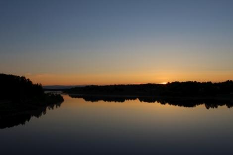 Keskiyön aurinko näkyy Kitisenjoen takana. Sillalle kannattaa jäädä yöllä tiirailemaan maisemia.