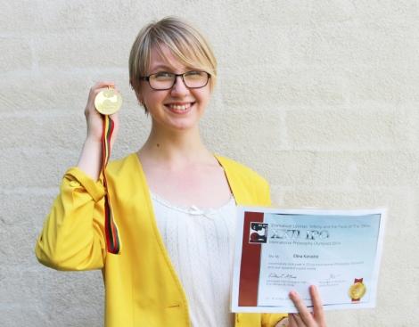 Elina esittelee kultamitaliaan ja kunniakirjaansa. Kuva: Antti Pentikäinen.