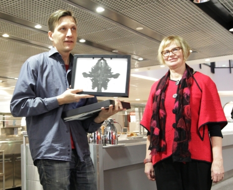 Maija Ferchen sai kuvataideopettaja Juha Rantaselta mustetahratestitauluja. Kuva: Heli Toivonen.